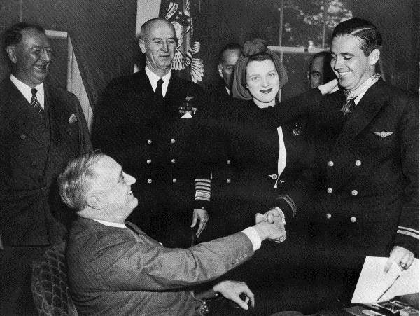 At left is Illinois State Society board member Frank Knox, a former publisher of the Chicago Daily News and Secretary of the Navy for President Franklin D. Roosevelt. FDR presents the Medal of Honor in 1942 to Navy pilot Butch O'Hare from Illinois. Sadly Butch was killed in action in 1943 and in 1949 the Orchard Field near Chicago was named O'Hare International Airport in his honor.
