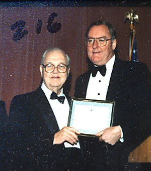 Mike Howlett and Gov. Thompson with Award Let to right: Former Illinois Secretary of State Michael J. Howlett (D-Chicago) receives the Illinois State Society Outstanding Public Service Award from the society's honorary Chair, Gov. James R. Thompson (R-Chicago) at the Society's Inagural Gala on Jan. 19, 1989.  Howlett and Thompson were opposing candidates for governor of Illinois in 1976. Mike Howlett had a long and distinguished record of public service to Illinois. He served as Illinois Auditor of Public Accounts for 12 years from 1961 to 1973 and as Secretary of State for four years from 1973 to 1977. As a young man, Mike played water polo for the Illinois Athletic Club and was on ten championship teams. He served in the Navy in World War II.