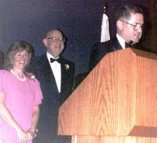 On Jan. 19, 1985, the Illinois State Society hosted its quadrennial nonpartisan Inaugural Gala at the National Press Club. Pictured at left is ISS officer Admiral Jim Carey, Chairman of the Maritme Commission, as he takes on master of ceremonies role at the 1985 Illinois State Society Inaugural Gala celebrating the second Inauguration of Illinois native President Ronald Reagan from Dixon. ISS board member Jeanne Jacob of Mendota is in back of the podium with another ISS officer.